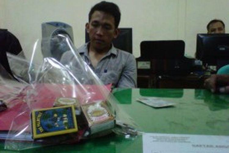 Pelaku pembobolan ATM diringkus petugas bersama barang bukti berupa korek api batang, Solo, Rabu(26/6/2013).