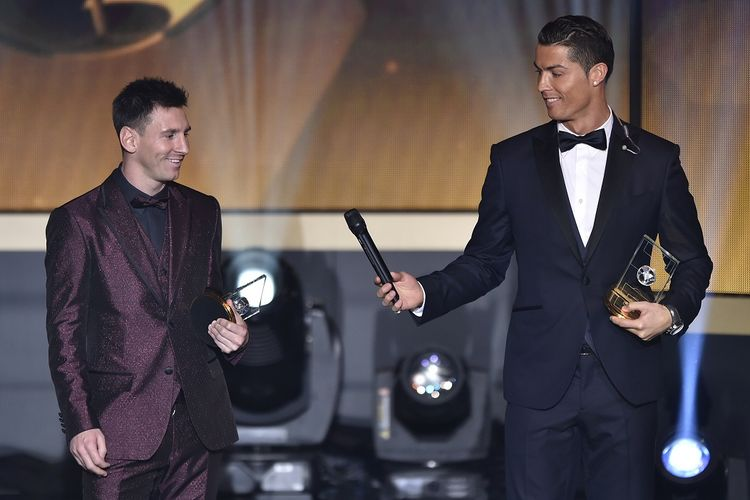 Pemain depan Real Madrid dan Portugal Cristiano Ronaldo memberikan microhpone ke Barcelona dan pemain depan Argentina Lionel Messi (kiri) ketika mereka berdiri di atas panggung setelah terpilih dalam FIFA FIFPro World XI 2014 selama upacara penghargaan FIFA Ballon dOr di Kongresshaus di Zurich pada 12 Januari