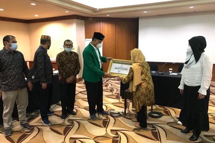Rektor Universitas Malikussaleh, Dr Herman Fithra, menyerahkan piagam penghargaan untuk Gus Dur, yang diterima putrinya Alisa Wahid di salah satu bangunan di Jakarta, Jumat (26/2/2021)