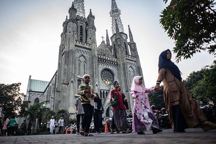Toleransi dan kebebasan beragama. Sejumlah warga berjalan menuju Masjid Istiqlal untuk melaksanakan Salat Idul Adha seusai memarkir kendaraan bermotornya di Gereja Katedral, Jakarta, Minggu (11/8/2019). Otoritas Gereja Katedral di Jakarta selain menyediakan halaman gereja sebagai tempat parkir bagi warga muslim yang melaksanakan Salat Idul Adha di Masjid Istiqlal juga mengubah jadwal ibadah misa Minggu dari pukul 06.00 WIB menjadi pukul 10.00 WIB untuk menghormati umat muslim yang merayakan Hari Raya Idul Adha pada Minggu, 11 Agustus 2019.