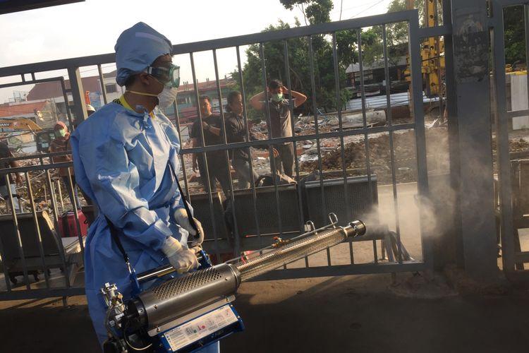 Petugas yang menyemprotkan cairan disinfektan di Stasiun Bekasi, Jawa Barat, Jumat (13/3/2020).