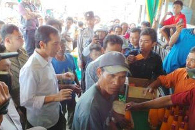 Gubernur DKI Jakarta Joko Widodo membagikan sembako bagi nelayan di Muara Angke, Jakarta Utara, Minggu (4/8/2013).