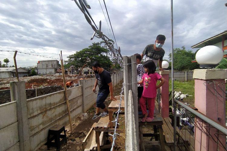 Dinding yang dibangun di depan gedung milik Asep memaksa keluarganya keluar rumah menggunakan tangga dan kursi. Ada pun lokasi dinding serta gedung tersebut berada di kawasan Tajur, Ciledug, Kota Tangerang, Banten.