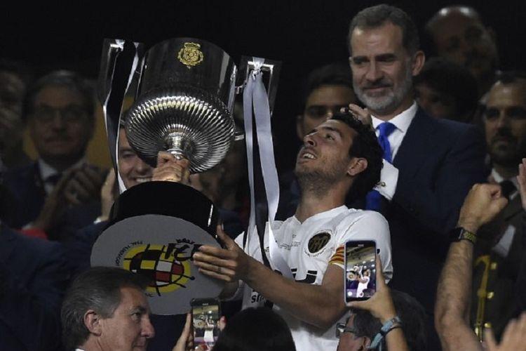 Kapten Valencia, Daniel Parejo, mengangkat trofi Copa del Rey seusai mengalahkan Barcelona pada laga final di Stadion Benito Villamarin, 25 Mei 2019.