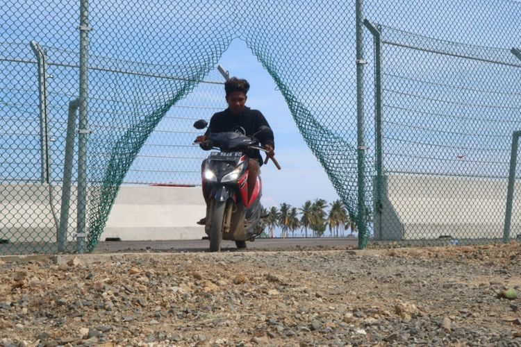 Salah seorang warga melintas pagar Sirkuit MotoGP Mandalika yang telah dirusak karena terancam terisolir