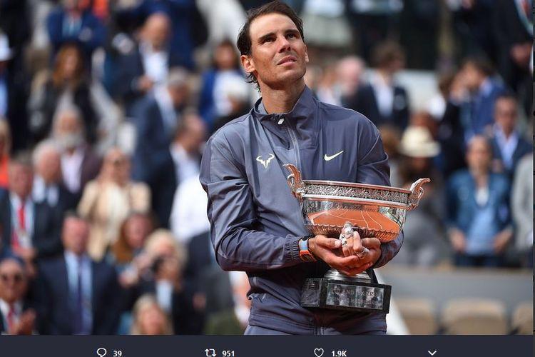 Petenis Spanyol, Rafael Nadal, menggenggam trofi French Open 2019 yang diraih setelah mengalahkan Dominic Thiem dalam laga final, Minggu (9/6/2019).