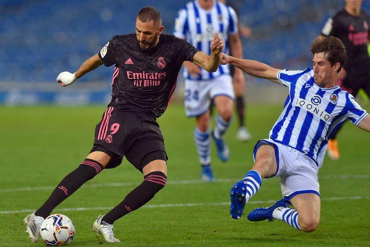 Penyerang Real Madrid, Karim Benzema, tengah berduel dengan bek Real Sociedad, Aritz Elustondo, pada pekan kedua Liga Spanyol, Senin (21/9/2020) dini hari WIB.