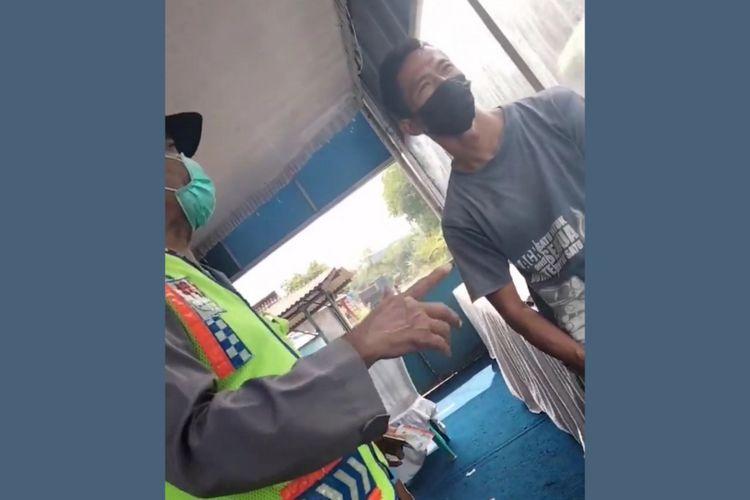 Tangkapan layar salah satu potongan video pria berseragam polisi melakukan negosiasi jumlah denda tilang dengan pengendara pelanggar lalu lintas, di Pos Check Point Penyekatan Kabuh, Kabupaten Jombang, Jawa Timur. Video tersebut sempat beredar di Facebook, Senin (31/5/2021).