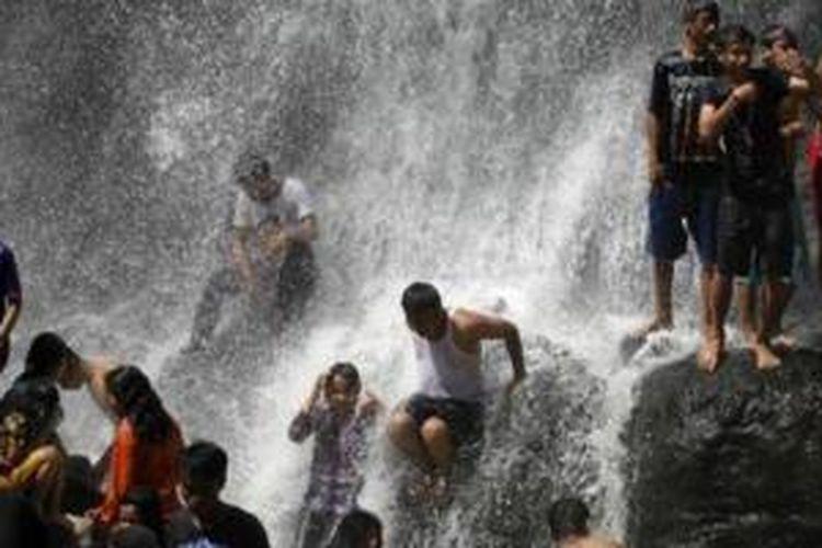 Pengunjung menikmati deburan Air Terjun Sindulang atau Curug Cinulang di Kampung Sindangwangi, Desa Tanjungwangi, Kecamatan Cicalengka, Kabupaten Bandung, Jawa Barat, Sabtu (25/8/2014).