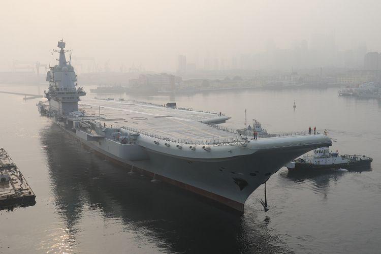 Foto yang diambil pada 13 Mei 2018 memperlihatkan kapal induk buatan dalam negeri pertama China, yang dikenal dengan Tipe 001A, ketika meninggalkan pelabuhan Dalian. China mengonfirmasi kapal induk tersebut sudah berlayar melewati Selat Taiwan untuk menggelar latihan rutin.
