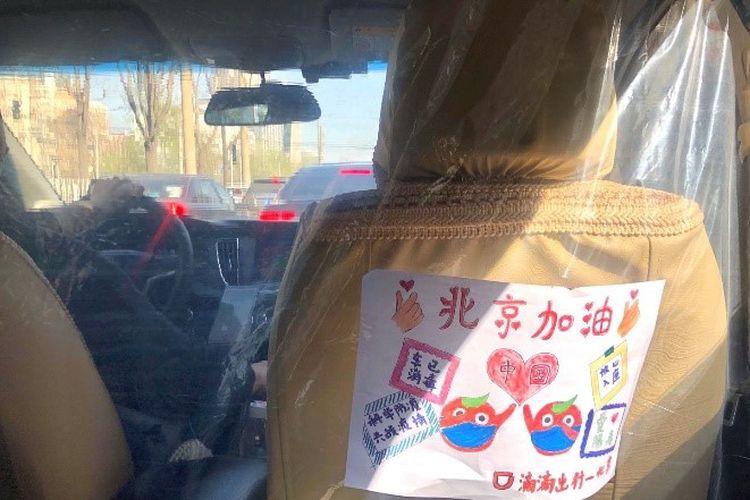 Penggunaan plastik sebagai pemisah antara penumpang dan pengemudi di China.