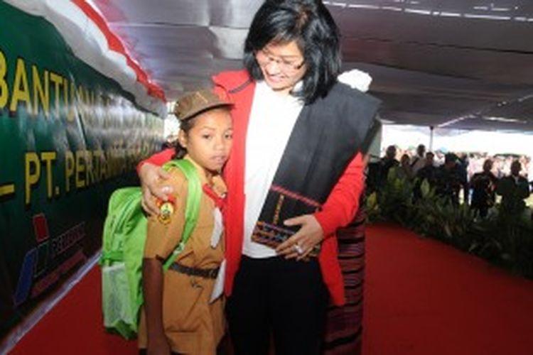Direktur Utama Pertamina Karen Agustiawan bersama seorang siswi SD Lamaknen, Kabupaten Belu, Nusa Tenggara Timur,  yang menerima bantuan peralatan sekolah.