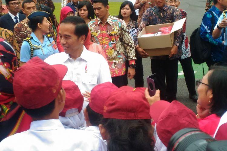 Presiden Joko Widodo menyalami murid SD yang menjadi peserta aubade Kongres Pancasila IX di Gedung Balairung UGM, Jalan Persatuan, Kabupaten Sleman, Sabtu (22/7/2017).