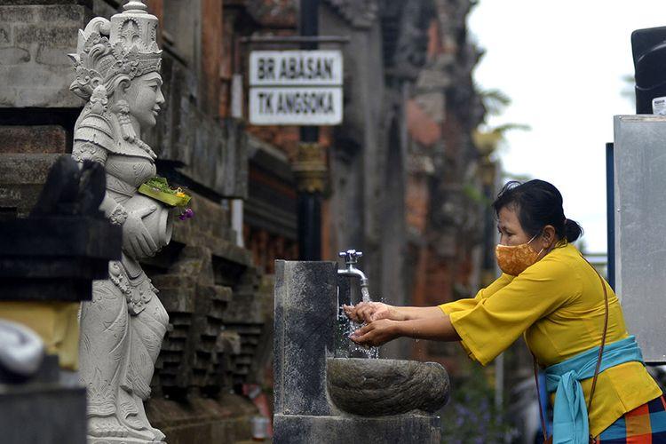 Umat Hindu mencuci tangan saat akan bersembahyang Hari Raya Galungan di Pura Jagatnatha, Denpasar, Bali, Rabu (16/9/2020). Perayaan Hari Raya Galungan yang merupakan hari kemenangan kebenaran (Dharma) atas kejahatan (Adharma) tersebut diikuti umat Hindu di Pulau Dewata dengan tetap menerapkan protokol kesehatan secara ketat untuk mencegah penyebaran pandemi COVID-19.