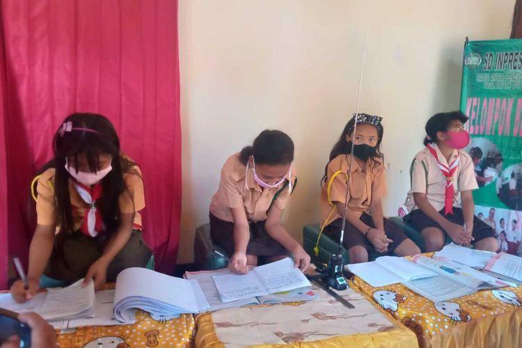 Murid Sekolah Dasar Inpres Liliba di Kecamatan Oebobo, Kota Kupang, Nusa Tenggara Timur (NTT), mengikuti proses belajar mengajar menggunakan Radio Handy Talkie (HT).