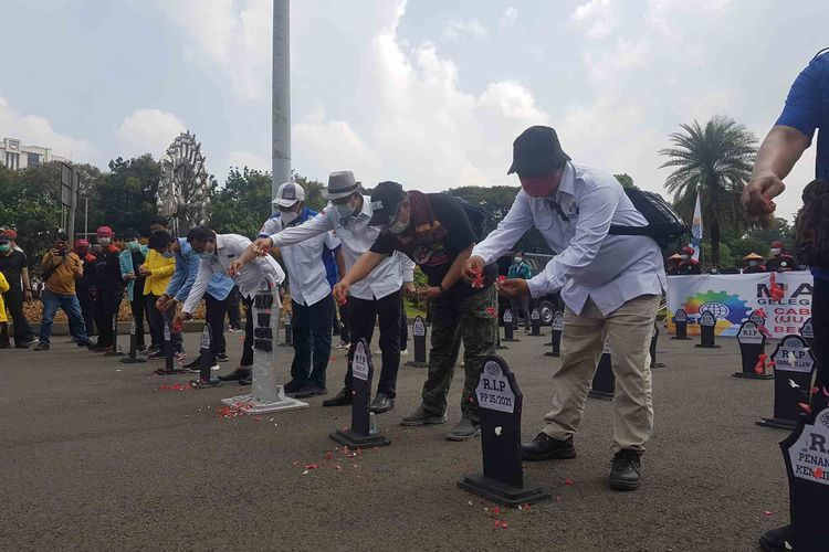 Massa buruh di Jakarta unjuk rasa melakukan aksi simbolis kubur omnibus law saat peringatan Hari Butuh Internasional 2021. Foto diambil pada Sabtu (1/5/2021)
