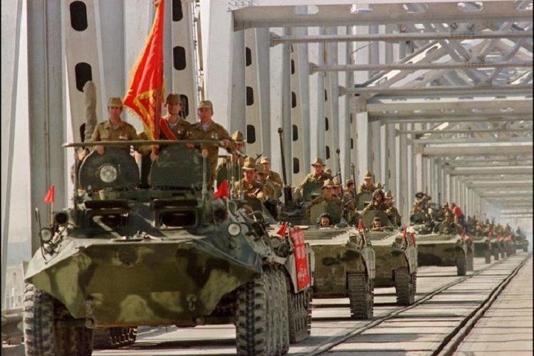 Konvoi kendaraan lapis baja pasukan Uni Soviet melintasi jembatan di perbatasan Soviet-Afghanistan saat mereka memutuskan menarik diri dari Afghanistan di Termez, Uzbekistan, pada 21 Mei 1988.