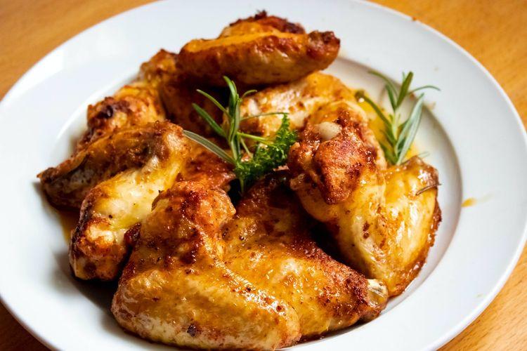 Ilustrasi sayap ayam goreng bertekstur renyah di luar dan lembut di dalam.