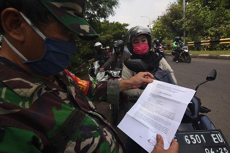 Petugas memeriksa surat izin keluar masuk (SIKM) Jakarta terhadap pengendara kendaraan bermotor yang melintas menuju Jakarta di perbatasan wilayah, Depok, Jawa Barat, Rabu (27/5/2020). Pemprov DKI Jakarta memberlakukan kebijakan SIKM Jakarta untuk mencegah potensi gelombang kedua COVID-19 di Ibu Kota.