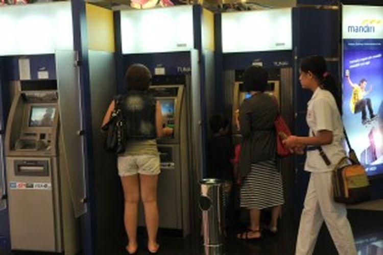 Pengambilan uang tunai di Anjungan Tunai Mandiri (ATM) Bank Mandiri, Jakarta