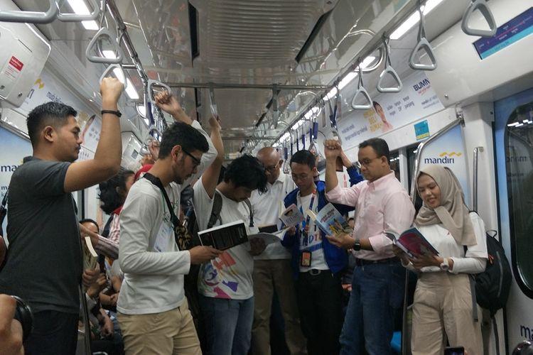 Gubernur DKI Jakarta Anies Baswedan membaca buku di dalam kereta MRT selama perjalanan dari Stasiun Bundaran HI menuju Stasiun Lebak Bulus, Minggu (8/9/2019).