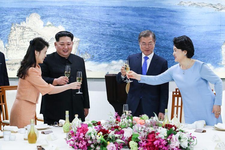 Pemimpin Korea Utara Kim Jong Un (dua dari kiri) didampingi oleh istrinya Ri Sol Ju (kiri), ketika bersulang dengan Presiden Korea Selatan Moon Jae In (dua dari kanan) dan Ibu Negara Kim Jung Sook (kanan) dalam jamuan makan malam saat KTT Antar-Korea Jumat (27/4/2018).