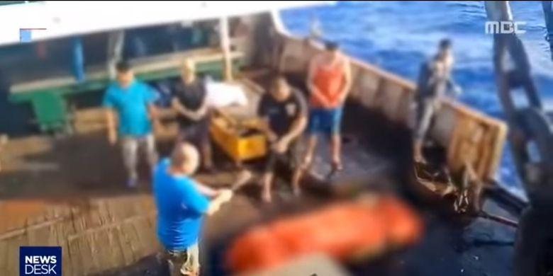 Sebuah tangkapan layar dari video yang dipublikasikan media Korea Selatan MBC memperlihatkan, seorang awak kapal tengah menggoyang sesuatu seperti dupa di depan kotak yang sudah dibungkus kain berwarna oranye. Disebutkan bahwa kotak tersebut merupakan jenazah ABK asal Indonesia yang dibuang ke tengah laut oleh kapal asal China.