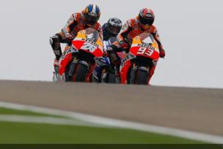 Pebalap Repsol Honda asal Spanyol, Dani Pedrosa (kiri), bersaing dengan rekan satu timnya, Marc Marquez (kanan), dan pebalap Movistar Yamaha, Jorge Lorenzo, untuk memimpin balapan pada GP Aragon, Minggu (28/9/2014).