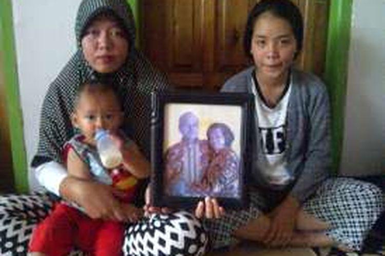 Kedua anak almarhum dan cucunya memperlihatkan foto Tia Agus Miharja semasa hidupnya bersama istrinya.