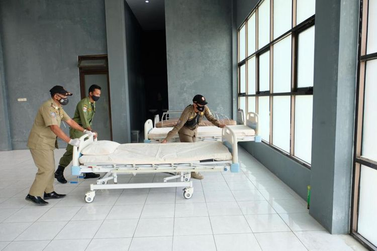Petugas sedang menata tempat tidur untuk pasien Covid-19 di rumah sakit darurat lapangan tenis indoor Gelora Sanden, Kota Magelang, Jumat (2/7/2021)
