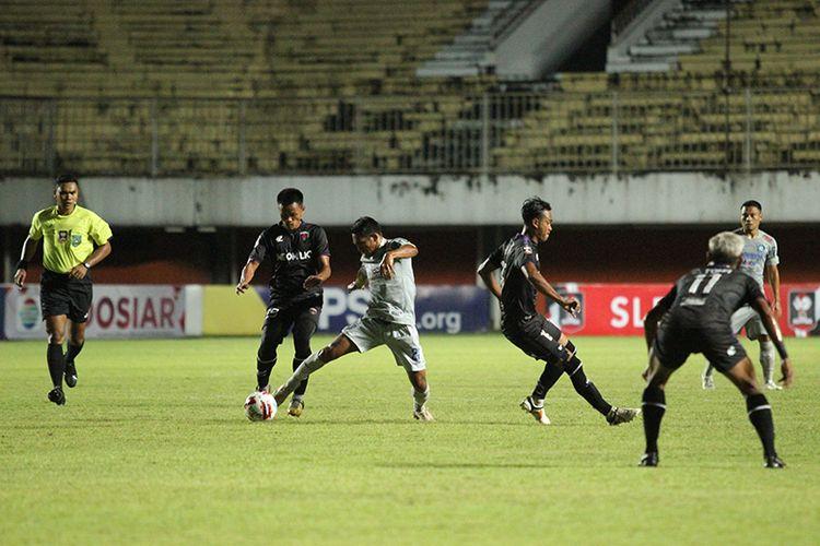 Pemain Persib Bandung, Frets Butuan (tengah) pergerakannya dikawal oleh salah satu pemain Persita Tangerang dalam pertandingan kedua penyisihan Grup D Piala Menpora 2021 di Stadion Maguwoharjo, Sleman, Senin (29/03/2021).