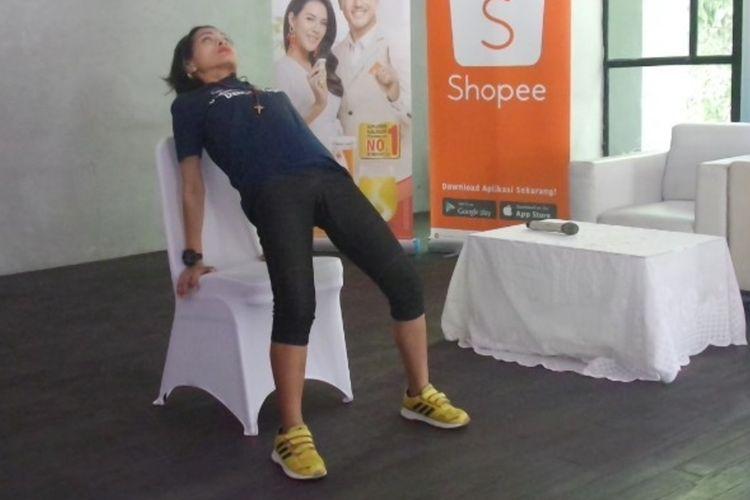Instruktur yoga Astrid Amalia saat memperagakan gerakan yoga sederhana di atas kursi untuk mencegah osteoporosis.