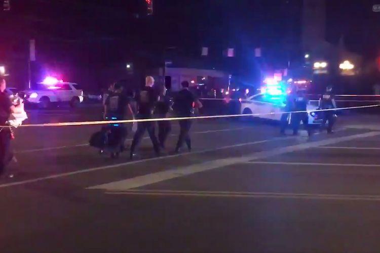 Potongan video ini diambil dari akun Twitter Derek Myers pada 4 Agustus 2019 memperlihatkan polisi berjalan di garis pengaman buntut terjadinya penembakan massal di kawasan bar dan tempat hiburan malam populer Oregon di Dayton, Ohio. Sebanyak 9 orang tewas dalam penembakan massal tersebut.