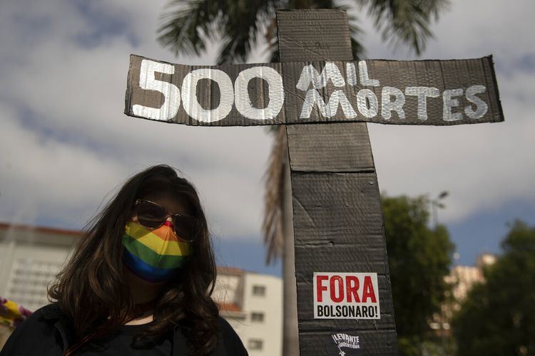 A woman, wearing a protective face mask, holds a sign in the shape of a cross with a message that reads in Portuguese;500 k deaths, during a protest against Brazilian President Jair Bolsonaro and his handling of the pandemic and economic policies protesters say harm the interests of the poor and working class, in Cuiaba, Brazil, Saturday, June 19, 2021. Brazil is approaching an official COVID-19 death toll of 500,000 ? second-highest in the world. (AP Photo/Andre Penner)