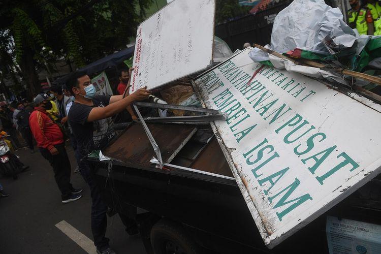 Petugas membongkar atribut-atribut saat melakukan penutupan markas  DPP Front Pembela Islam (FPI) di Petamburan, Jakarta, Rabu (30/12/2020). Polisi dan TNI menutup markas FPI setelah pemerintah memutuskan untuk membubarkan organisasi pimpinan Rizieq Shihab itu. ANTARA FOTO/Akbar Nugroho Gumay/nz