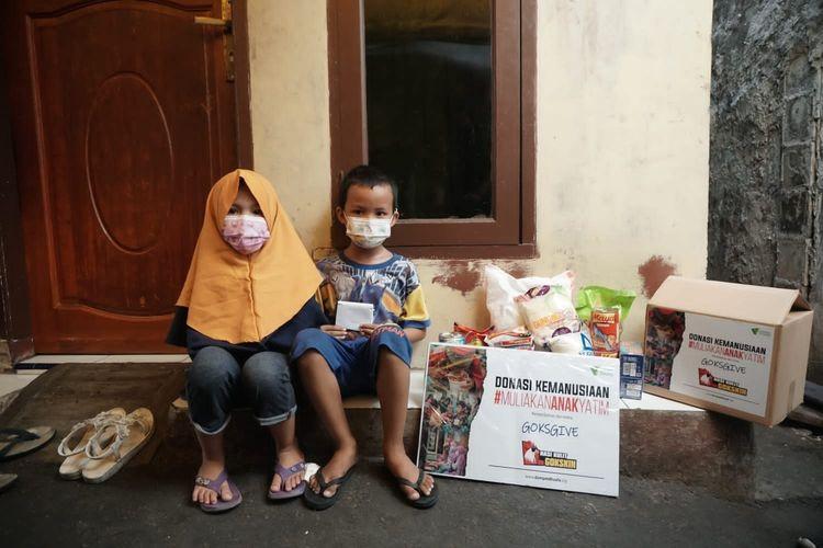 Putra dan Cahaya, penerima manfaat donasi kemanusiaan Muliakan Anak Yatim Dompet Dhuafa, saat menerima paket bantuan, beberapa waktu lalu.
