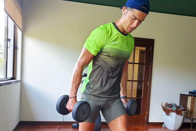 Cristiano Ronaldo melakukan latihan lunges dengan beban di kedua tangannya.