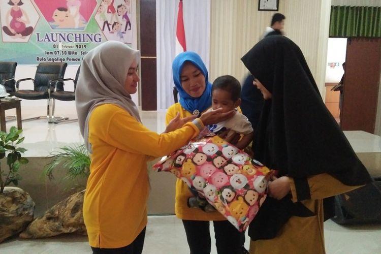 Bupati Luwu Utara Indah Putri Indriani saat memberikan hadiah kepada bayi korban gempa bumi dan likuefaksi Palu, Sabtu (02/02/2019)