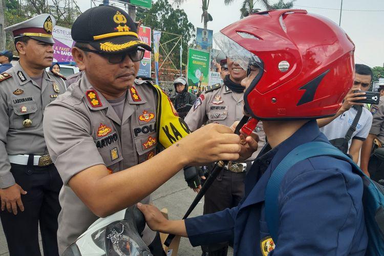 Polres Sumedang membagikan helm gratis kepada mahasiswa di depan kampus Unpad Jatinangor, Sumedang, Jawa Barat, Kamis (10/10/2019) siang. AAM AMINULLAH/KOMPAS.com