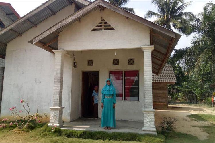 Ibu Asraf, Atik, berdiri di depan rumahnya yang sudah dibedah pemerintah setempat di Desa Bina Baru, Kecamatan Kampar Kiri Tengah, Kabupaten Kampar, Riau, Rabu (14/8/2019). Asraf salah satu Paskibraka nasional perwakilan Riau.