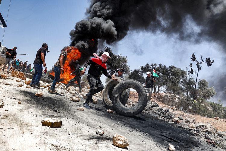 Pedemo Palestina membakar ban dalam bentrokan dengan tentara Israel di desa Beita, selatan Nabius, Tepi Barat, pada Jumat (11/6/2021).