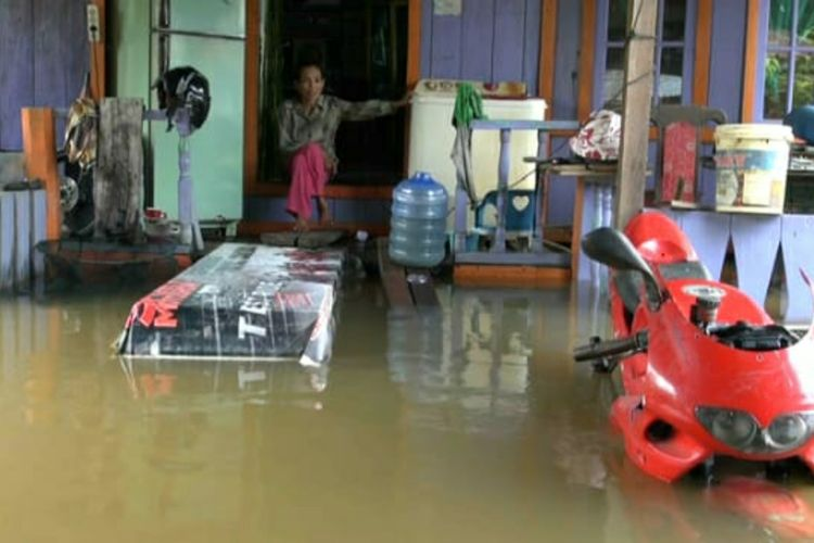 Siti Aminah (54) duduk di pintu masuk rumahnya yang digenangi banjir di Desa Buluh Cina, Kecamatan Siak Hulu, Kabupaten Kampar, Riau, Kamis (19/12/2019). Satu unit sepeda motor Ninja di depan rumahnya ikut terendam banjir, karena tak sempat dievakuasi.