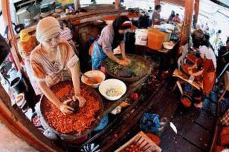 Tiga perempuan menggiling belasan kilogram cabai setiap hari di Pasar Ibuh Timur, Payakumbuh, Sumatera Barat, Rabu (10/7/2013). Hanya dengan cabai yang digiling menggunakan tangan, rendang terlezat bisa dihasilkan. Para koki di Istana Silinduang Bulan, Batusangkar, juga menggunakan cabai giling seperti ini untuk membuat rendang yang akan disajikan kepada sultan, presiden, dan pejabat yang bertandang ke sana.
