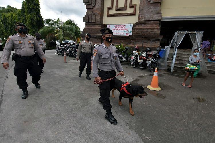 Anggota Unit Satwa K9 Polda Bali melakukan patroli pada masa perpanjangan Pemberlakuan Pembatasan Kegiatan Masyarakat (PPKM) di Pasar Badung, Denpasar, Bali, Rabu (27/1/2021). Pemerintah Provinsi Bali memperketat PPKM jilid 2 dengan memajukan pembatasan jam operasional dari pukul 21.00 WITA menjadi pukul 20.00 WITA mulai Selasa (26/1/2021) hingga Senin (8/2/2021) mendatang. ANTARA FOTO/Nyoman Hendra Wibowo/hp.