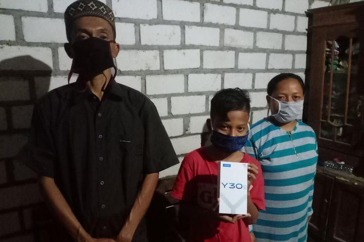 Dimas Ibnu Alias (tengah) menunjukkan smartphone yang diterima dari Vivo Indonesia. Dia diapit oleh ayahnya, Didik Suroyo (kiri) dan ibunya, Asiatun.