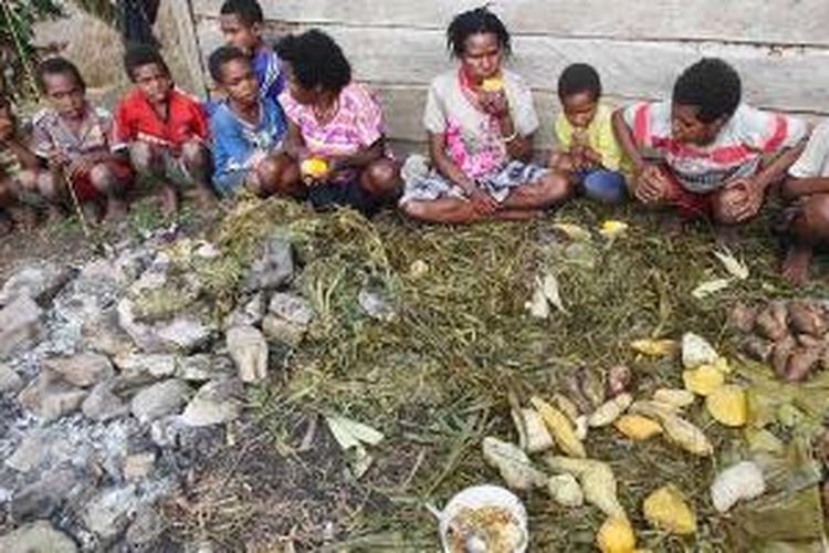 Warga bersama-sama menikmati jagung dan ubi yang telah dimasak dengan bakar batu di samping rumah keluarga di Kampung Hepuba, Distrik Asolokobal, Jayawijaya, Papua, Minggu (8/12/2013).