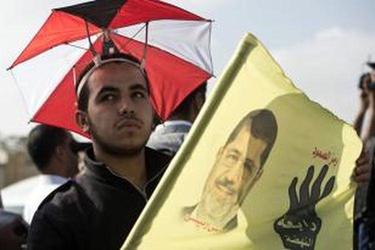 Seorang pendukung Muhammad Mursi membawa sebuah bendera bergambar wajah presiden Mesir terguling itu di luar kompleks akademi kepolisian Kairo lokasi sidang pengadilan Mursi, Senin (4/11/2013).