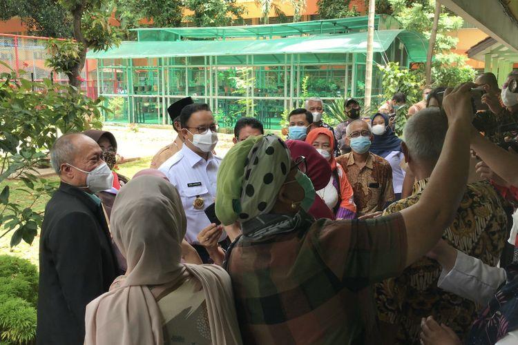 Kehadiran Gubernur DKI Jakarta Anies Baswedan ke lokasi vaksinasi Covid-19 menarik perhatian para perwakilan guru, tenaga pendidikan, dan dosen dari wilayah Jakarta dan sekitarnya di SMAN 70, Kebayoran Baru, Jakarta Selatan pada Rabu (24/2/2021).
