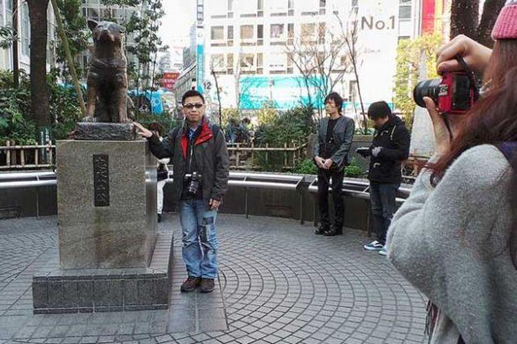 Seorang wisatawan berfoto di samping patung anjing Hachiko di dekat Stasiun Shibuya, Tokyo, Jepang.