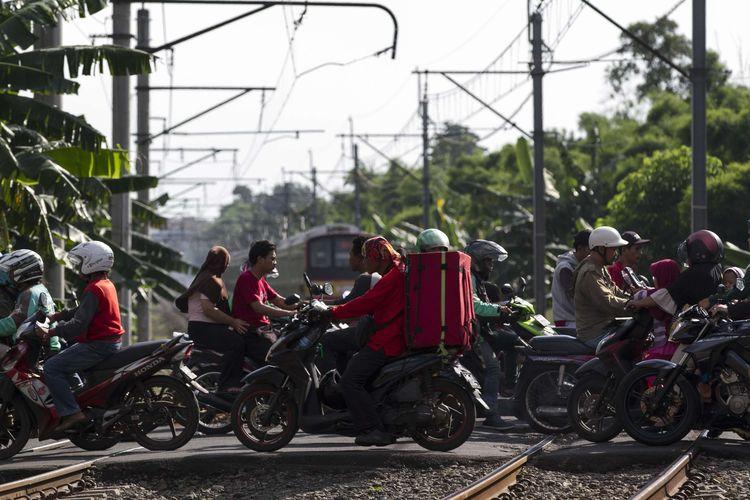 Pengguna jalan melintas di perlintasan kereta api di wilayah Bumi Bintaro Permai, Pondok Aren, Jakarta Selatan, Minggu (23/2/2020). Tidak berfungsinya palang pintu di perlintasan kereta api sejak 2 tahun lalu mengancam keselamatan warga.